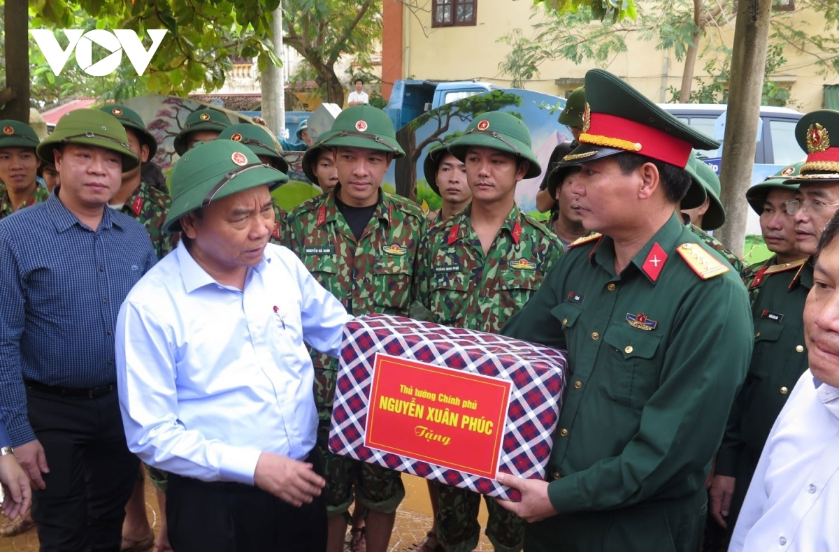 PM phuc highlights the great efforts put in by relevant forces from ministry of national defence and public security as they participate relief rescue to protect lives property local citizens. pictured is pm presenting gifts officers soldiers military region 4
