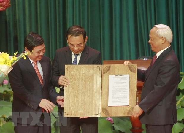 Vice NA Chairman Uong Chu Luu (R) hands over NA Standing Committee's resolution on organising administrative units at the district and commune levels and establishing Thu Duc city to HCM City (Source: VNA)