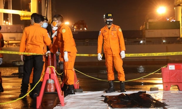 Officials check a fragment believed to be of Indonesian Sriwijaya Airlines flight number SJ182. (Photo: Getty Images)