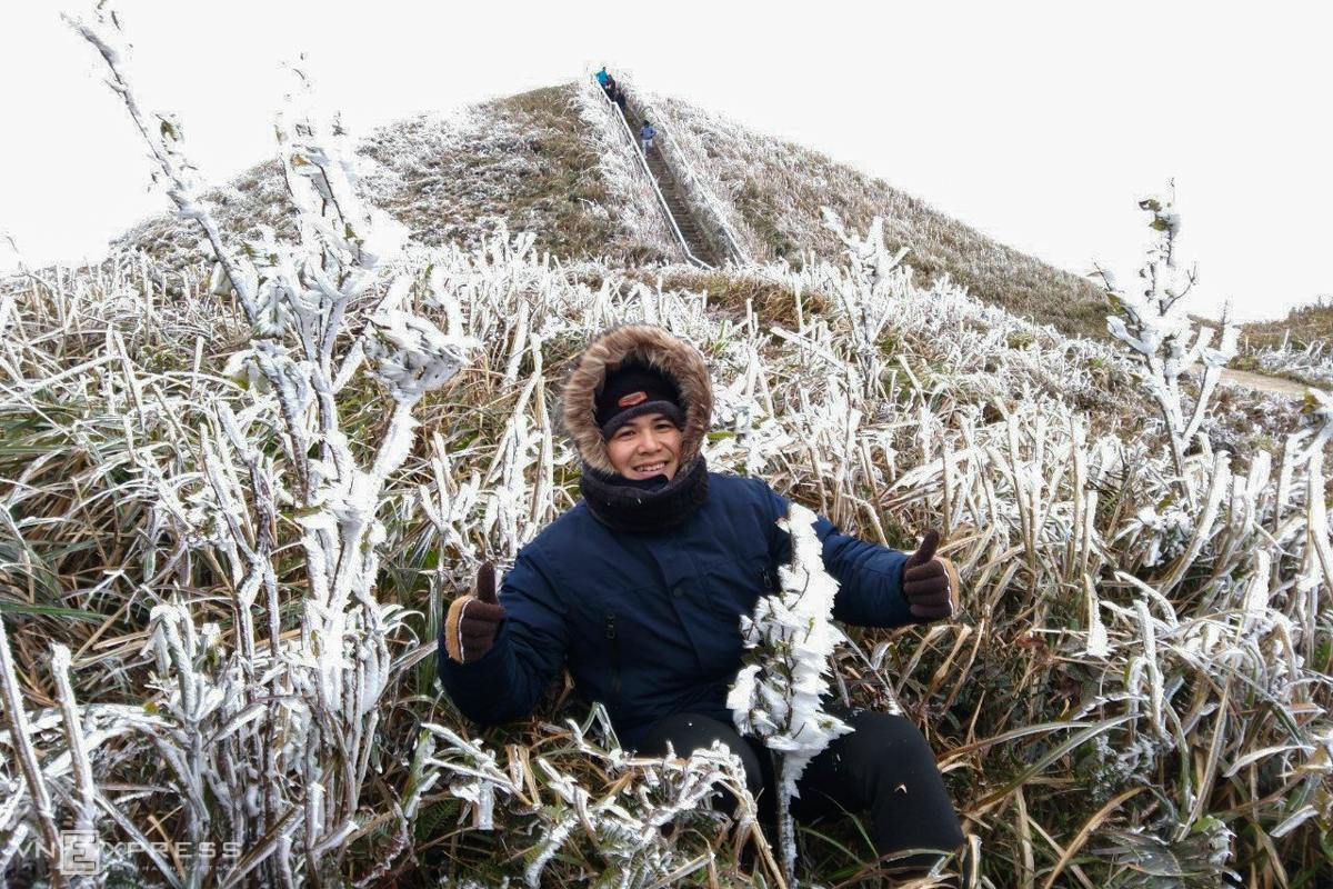 A tourist takes a check-in photo amidst the frosted grass. Given the strong cold, the man is all bundled up in a thick layer of coats (Photo: VNE)