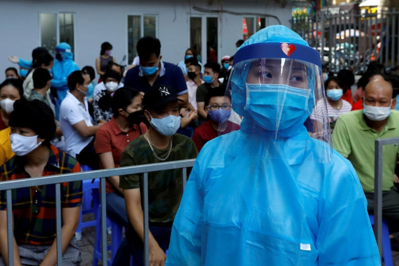 A healthcare worker wearing protective suit walks past as local residents wait at a coronavirus disease (covid-19) testing center in hanoi, vietnam aug 10, 2020. (reuters)