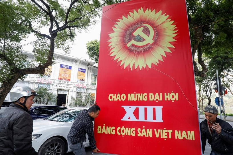 Workers set up a poster for upcoming 13th National Congress of the ruling Communist Party of Vietnam, on a street in Hanoi, Vietnam January 12, 2021.