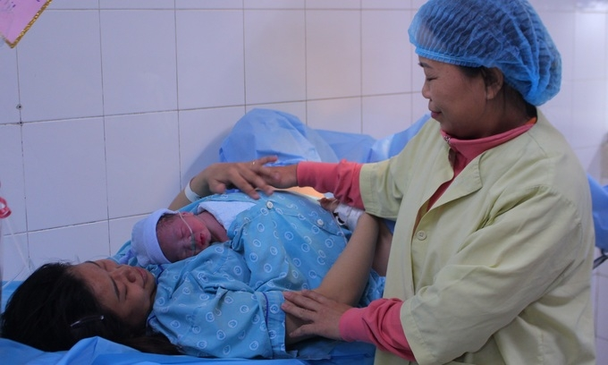 A family member helps a woman hold her new-born son at Tu Du Hospital in HCMC, January 2020.