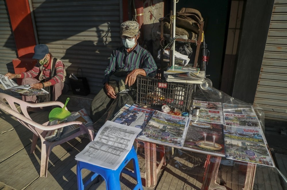One man reading newspaper at a newsstand in yangon, myanmar on february 2 (photo: ap)