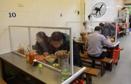 Hanoi restaurants install table partitions to curb COVID-19