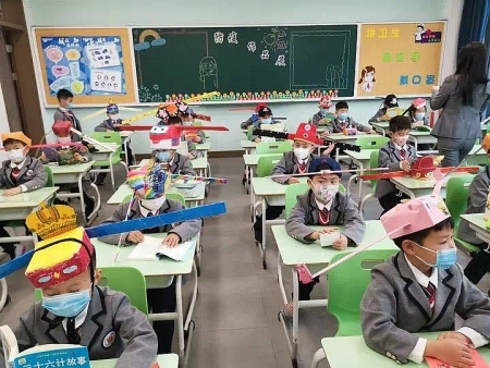 Chinese primary students return schools with self-made 'distancing hats'