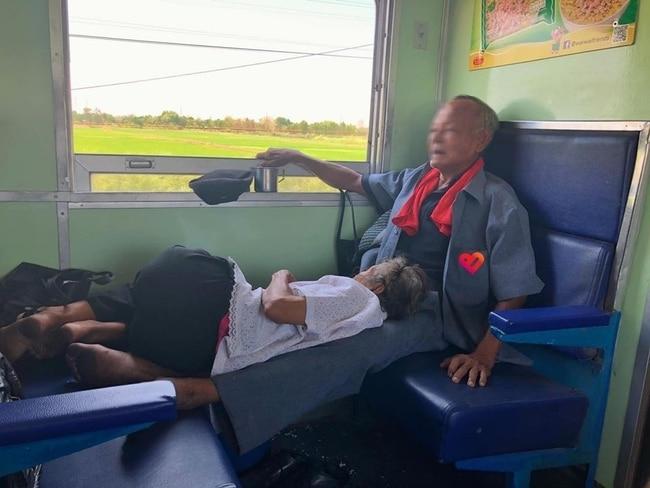 Melting heart photo of old woman slumbering on husband's legs on Vietnam's train