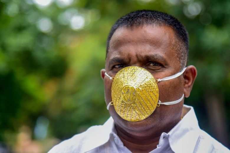 weird covid 19 style indian man wears gold face mask to shield from coronavirus