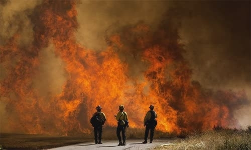 Firefighters look at the fire of an Apple fire in Cherry Valley, California, on August 1