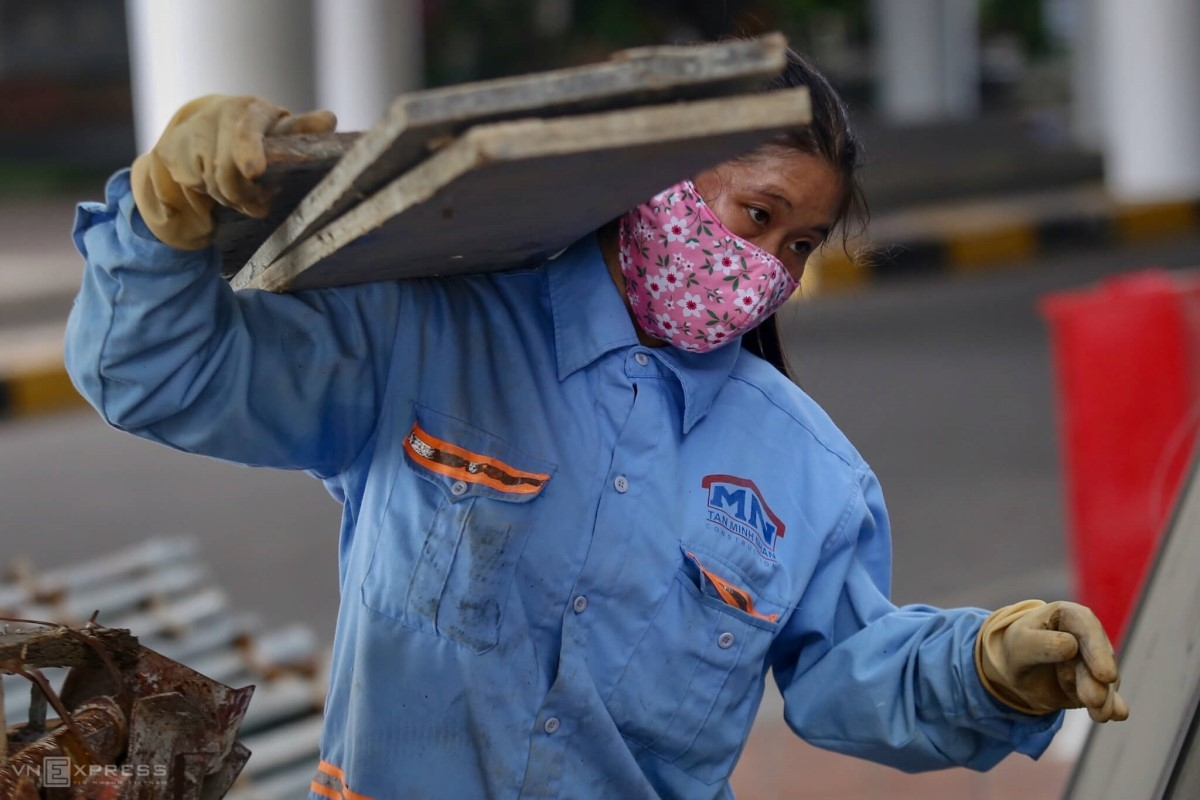 A worker carries a stack of sheets on her shoulders.