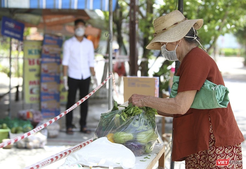 A lady takes a bagful of foods from the zero dong food store