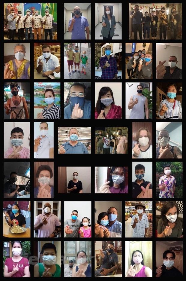 expats in vietnam join hands in face masks wearing promotion campaign
