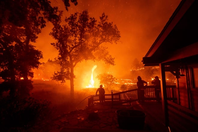 Firefighters watch flames from the LNU Lightning Complex fires approach a home in the Berryessa Estates neighborhood of unincorporated Napa County, Calif., on Friday, Aug. 21, 2020. The blaze forced thousands to flee and destroyed hundreds of homes and other structures.