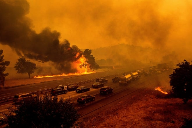 Flames from the LNU Lightning Complex fires jump Interstate 80 in Vacaville, Calif., Aug. 19, 2020. The highway was closed in both directions shortly afterward.