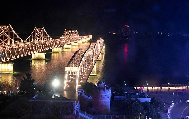The building is seen on the far side of the Amnok river in North Korea by the side of a border bridge, left, in Dandong, China, in July. (Yoshikazu Hirai)