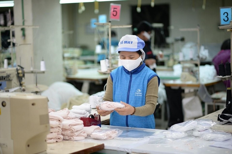 An assembly-lined worker packaging face masks in Vietnam