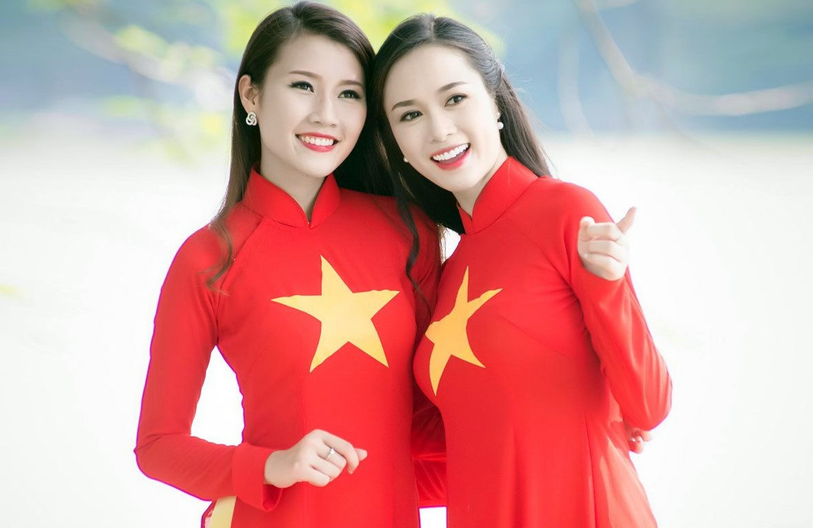 Two women wearing Ao Dai in the colors and images of Vietnam's national flag (Photo: Redsvn)