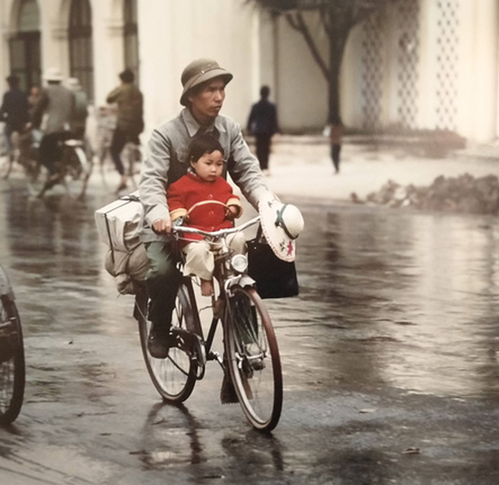 A father carrying his daughter on a bicycle (Photo courtesy of Thomas Billhardt/ via Zing News)