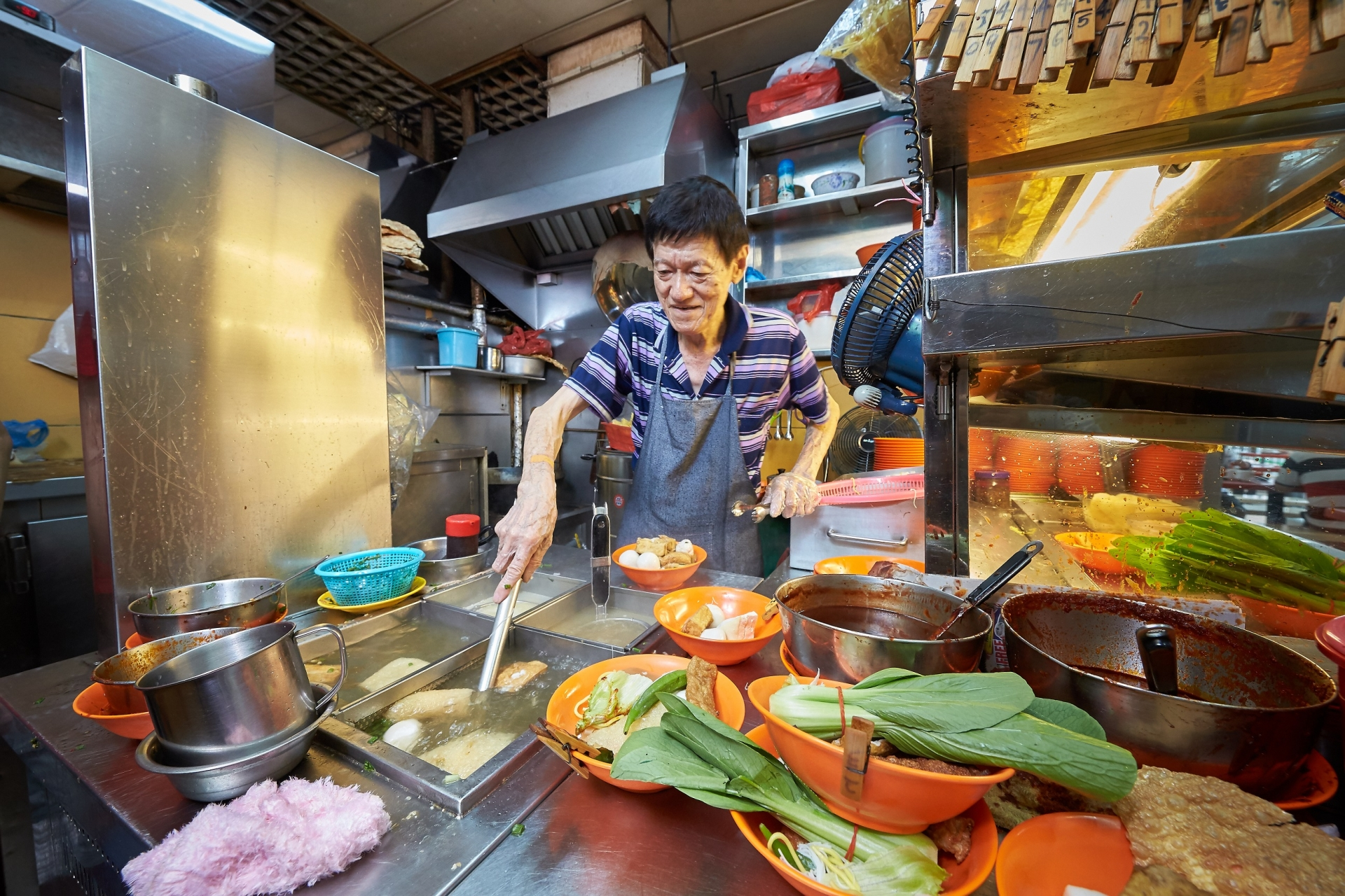 A Singaporean vendor making food at his hawker (Photo: Oursg Heritage)