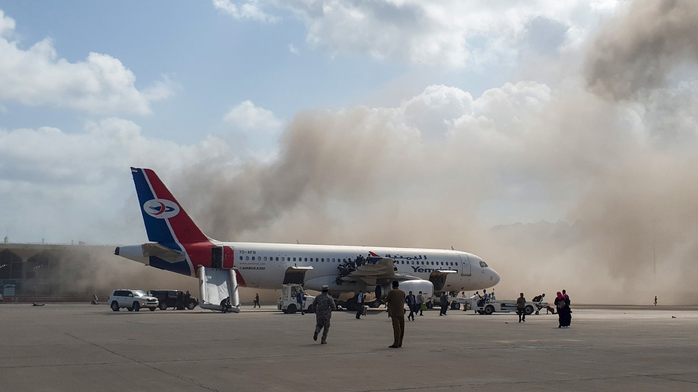 Smoke billows behind a plane that brought Yemen's new government to Aden International Airport on Wednesday. Explosions rocked the airport shortly after the plane arrived. (Photo: AFP)