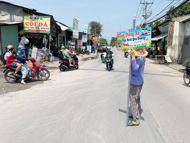 62-year-old lady holds traffic sign to help students pass the road in Ho Chi Minh city, video