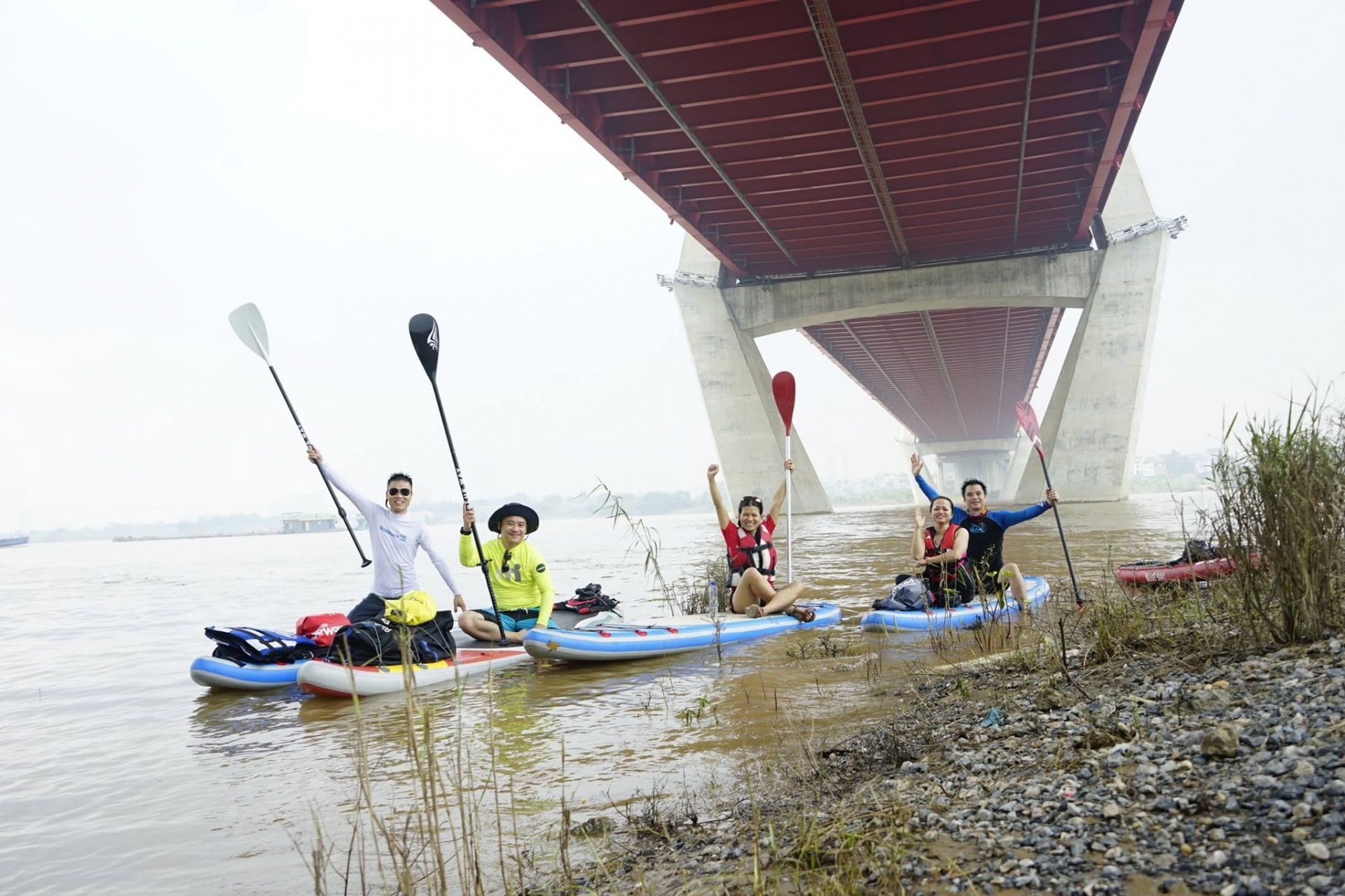 Young people in Hanoi try paddle boarding on Red river