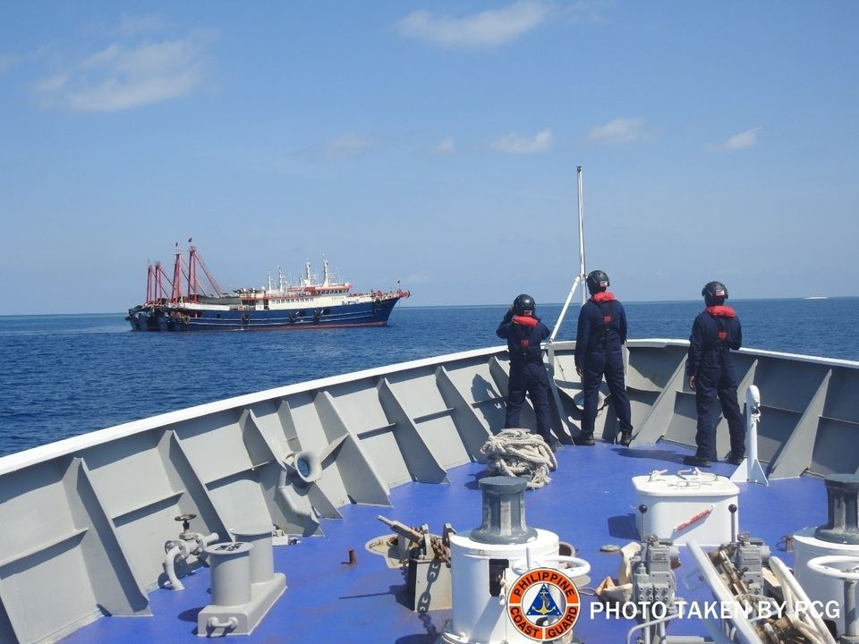 Philippine Coast Guard personnel survey several ships believed to be Chinese militia vessels in Sabina Shoal in the South China Sea on April 27, 2021 [File: Philippine Coast Guard/H