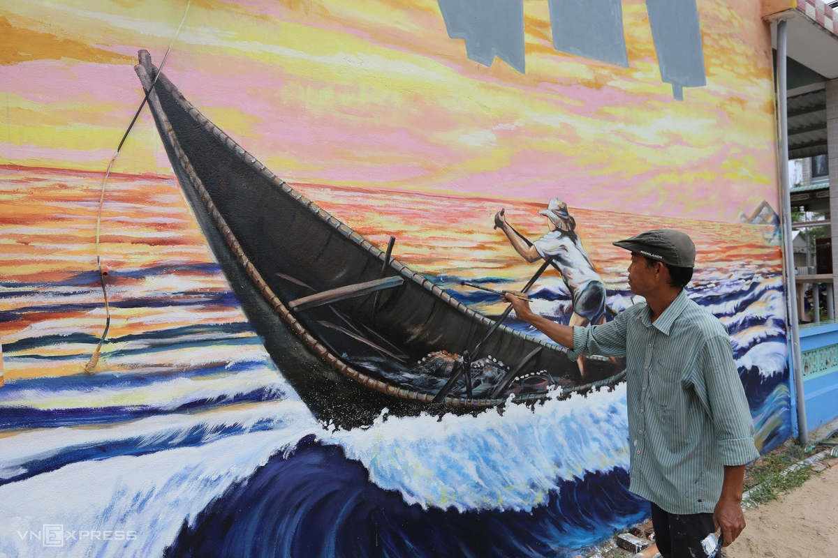 Artist Pham Dinh Hai is drawing a mural with 15m in length and 5m in width on the wall of a local house. His painting features coastal village's residents riding boats to catch fish.