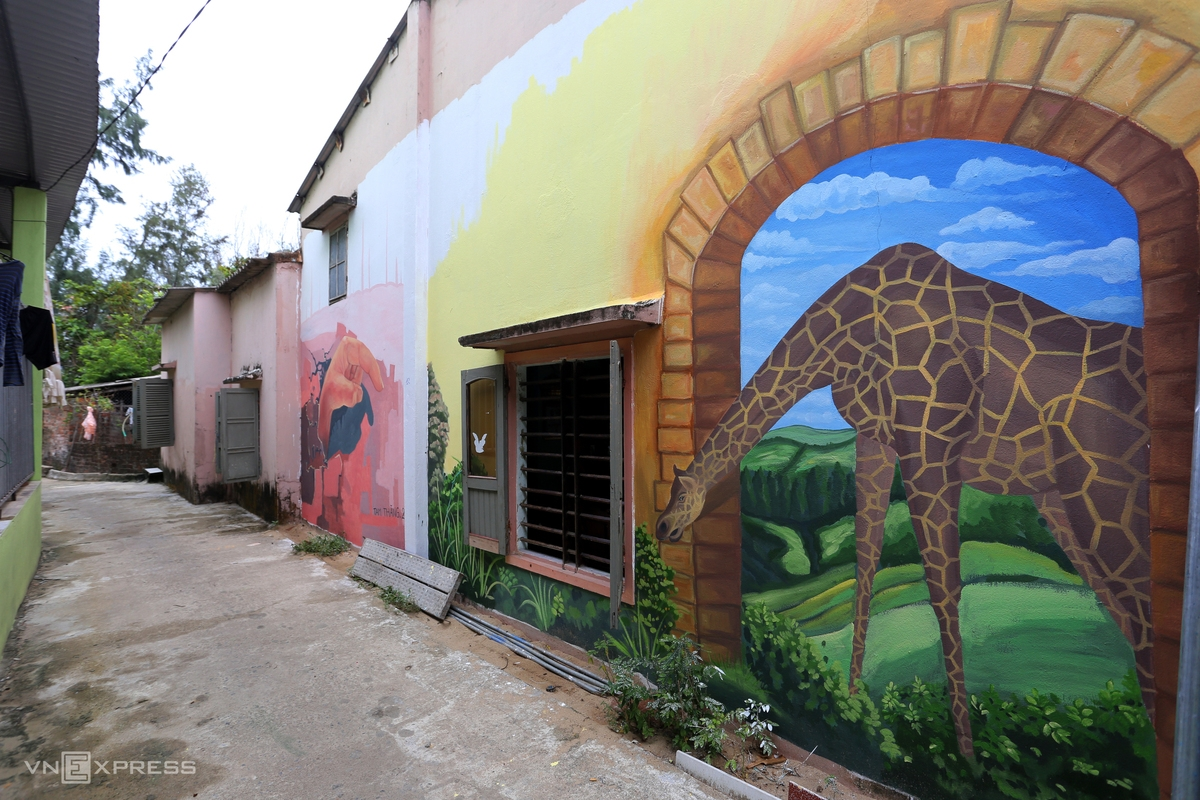 The wall of a narrow alley is covered with murals.
