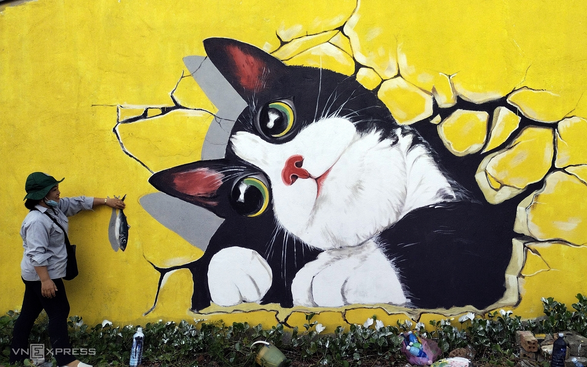 A visitor takes a picture of the hand-painting fish feeding cats on the wall.