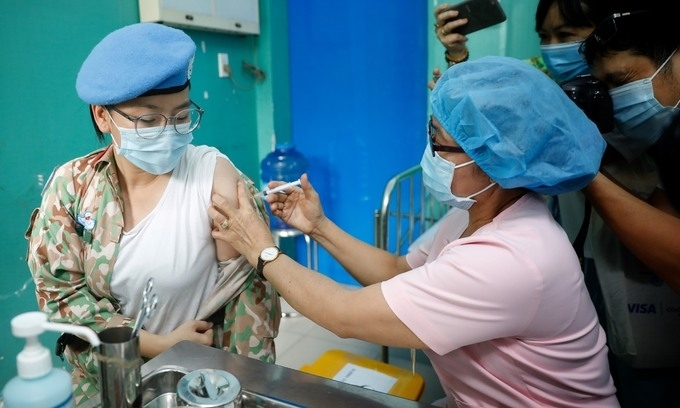 A Vietnamese military medic receives her first shot of Covid-19 vaccine. Photo by VnExpress