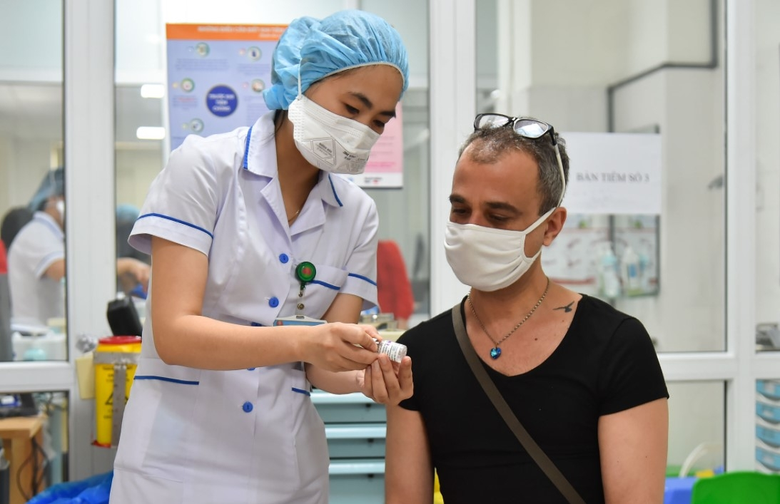 A medical worker explains pre-vaccination guidelines to a foreigner on June 10. Photo Bao Quoc Te