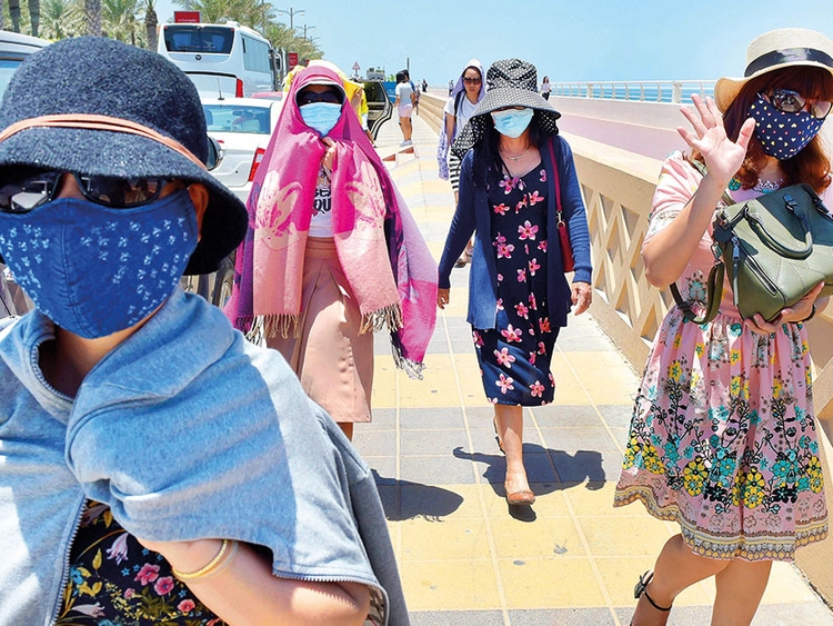 Tourists cover their faces to save themselves from the scorching sun in Dubai.