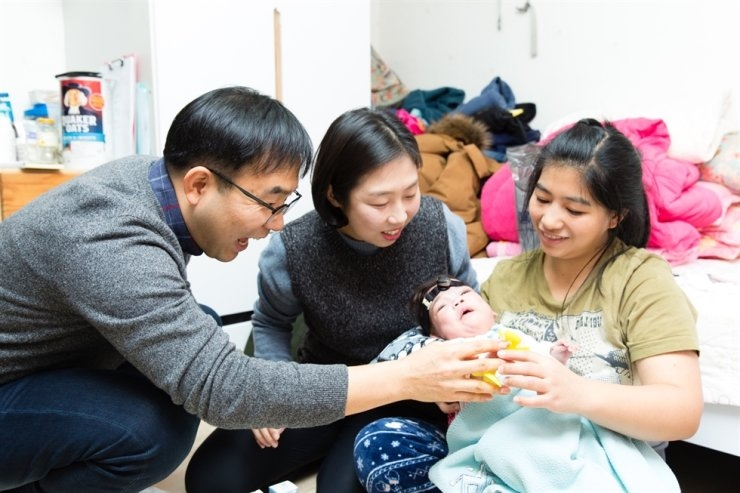 Cheong Jong-won, a pastor, and his wife Kim Sung-eun visit a woman and her baby at her home in Seoul in this March 2018 photo. Courtesy of Light and Salt