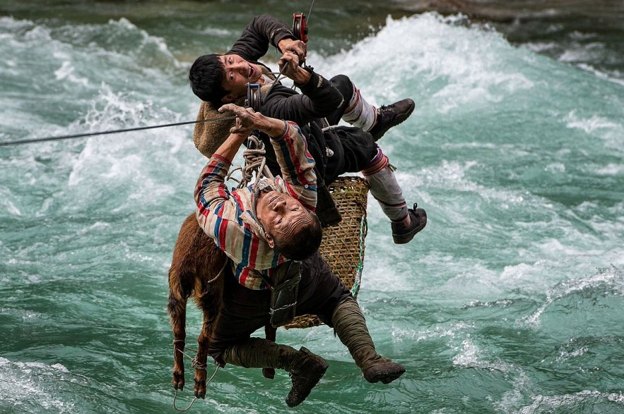 Two men use a zipline to transport animals and good across the river in Yunnan, China, May 2021. Photo by Minqiang Lu/The Nature Conservancy