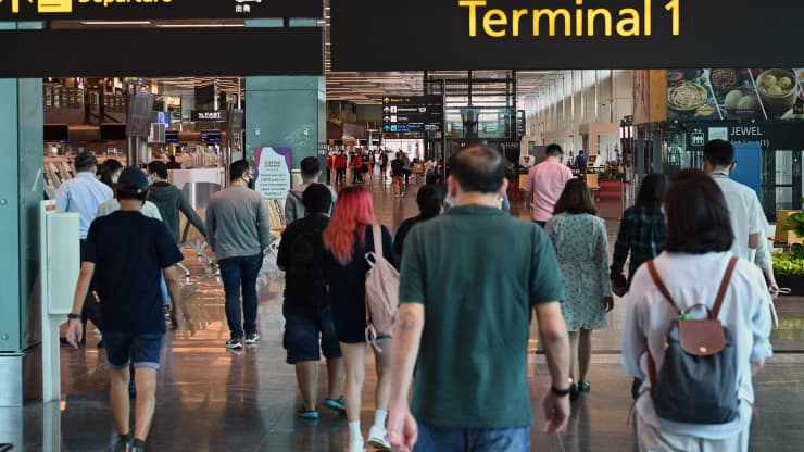People walk toward the departure hall at Changi International Airport in Singapore on March 15, 2021. Roslan Rahman | AFP | Getty Images