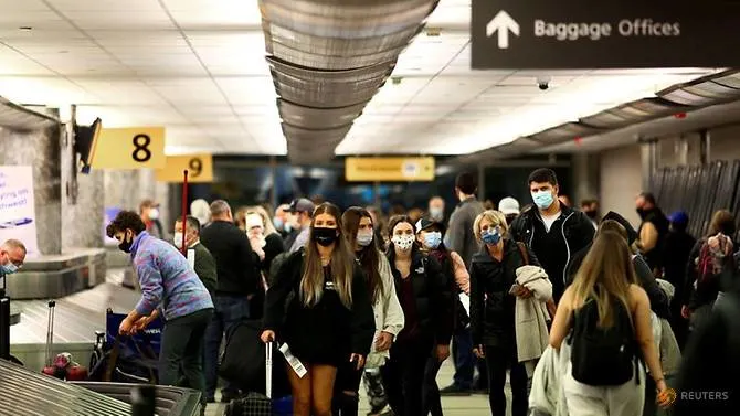 Travelers wearing protective face masks to prevent the spread of COVID-19 reclaim their luggage at the airport in Denver, Colorado, US on Nov 24, 2020. (Reuters/Kevin Mohatt)