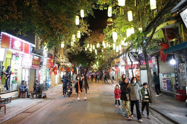 Local residents stroll along a pedestrian street in Hanoi. The capital city will hold a festival to promote its tourism and culinary culture from April 16 to 18 – PHOTO: VNA