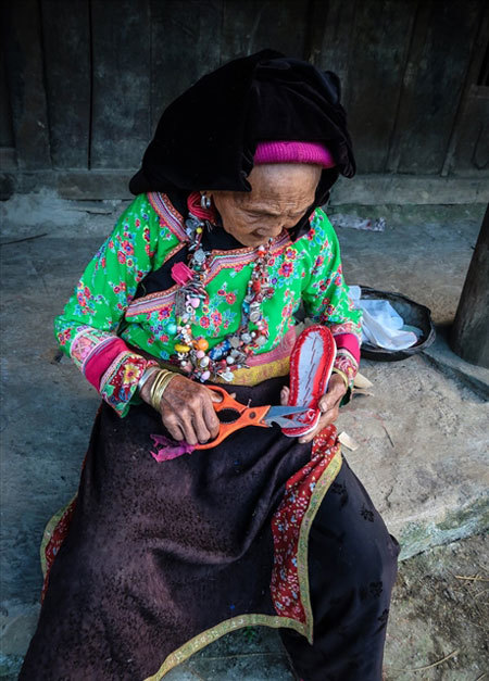 LOCAL LIVELIHOOD: An elderly Xa Phang woman making embroidered shoes outside her home. Photo laodong.vn