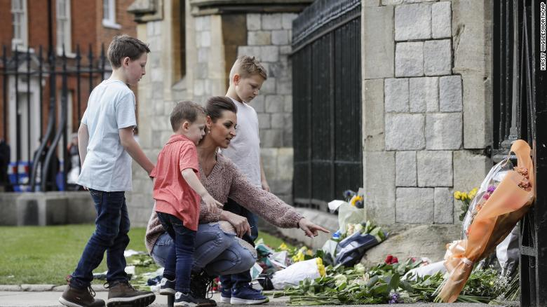 A family put flowers outside Windsor Castle (Photo: CNN)