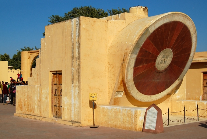 """The Samrat Yantra in Jaipur is part of the Jantar Mantar (translation: instruments for calculation), a Big Collection of 14 devices built for measuring time, for astronomy, and for astrology, in the 18th century. Historical accounts say that, in 1719, Mogul emperor Mohammad Shah was leaving on an expedition. But the planets, weren't in the """"right"""" spots in the night sky. This misalignment due to failed predictions spurred Maharajah Sawai Jai Singh II to build a series of observatories. When Singh decided to move and found a new city (what would be Jaipur) in a nearby valley, he also had a new observatory built there."""