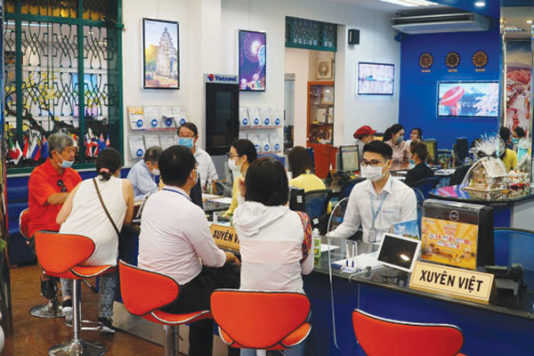 Local residents look for summer tours at a travel agency. Photo courtesy of nld.com.vn