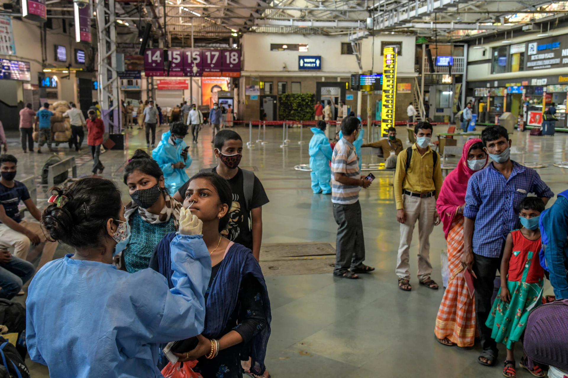 Health workers testing recent arrivals at a train station in Mumbai earlier this month. (Photo: New York Times)
