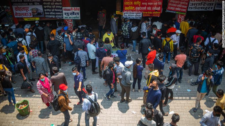 People wait to board a bus back to their home villages after new government restrictions in Kathmandu, Nepal, on April 27. (Photo: CNN)