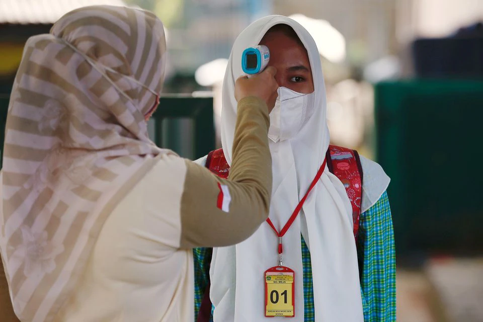 An elementary school student wearing a face mask has her temperature checked before attending a classroom session, as schools reopen amid the coronavirus disease (COVID-19) pandemic in Bekasi, on the outskirts of Jakarta, March 24, 2021. REUTERS/Willy Kurniawan
