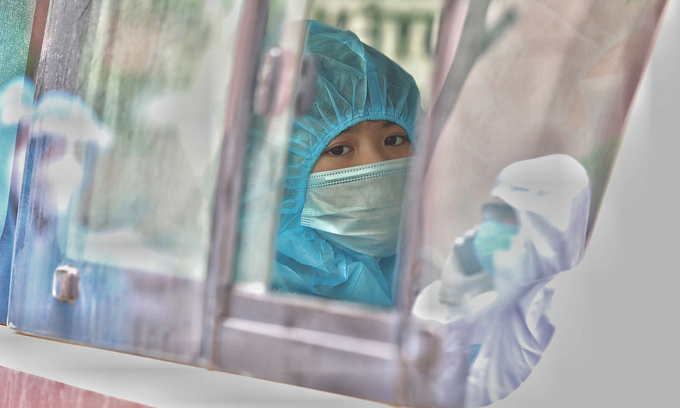 A person wears a protective suit on a bus at a Covid-19 locked down zone in Hanoi, with reflections of medical workers on the windows, May 13, 2021. Photo by VnExpress/Ngoc Thanh.