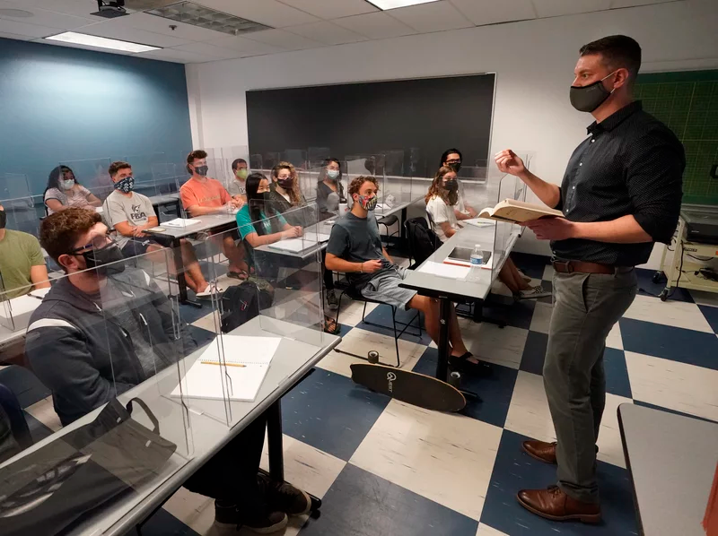 The CDC announced Thursday that fully vaccinated people can safely stop wearing masks indoors and outdoors. Kyle Faircloth teaches a class at Palm Beach Atlantic University in West Palm Beach, Fla., in February. Wilfredo Lee/AP