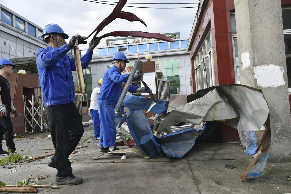Workers clear debris at a factory that was damaged by a reported tornado in Shengze township in Suzhou in eastern China's Jiangsu Province, Saturday, May 15, 2021. Two tornadoes killed several people in central and eastern China and left hundreds of others injured, officials and state media reported Saturday. (Chinatopix via AP)