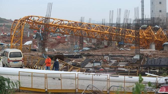 People stand near a toppled crane at a construction site after a tornado hit an economic zone in Wuhan in China's central Hubei province on May 15, 2021. (Photo: AFP)