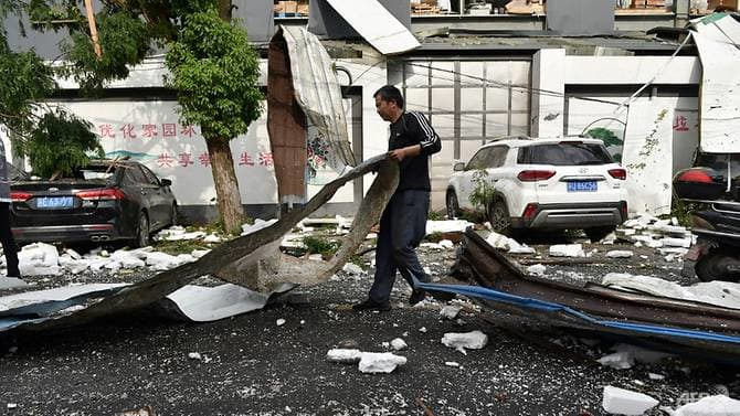 A man cleans up damage after a tornado hit the city of Suzhou in China's eastern Jiangsu province province on May 15, 2021. (Photo: AFP)